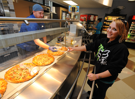 A student getting a pizza from a cafe employee
