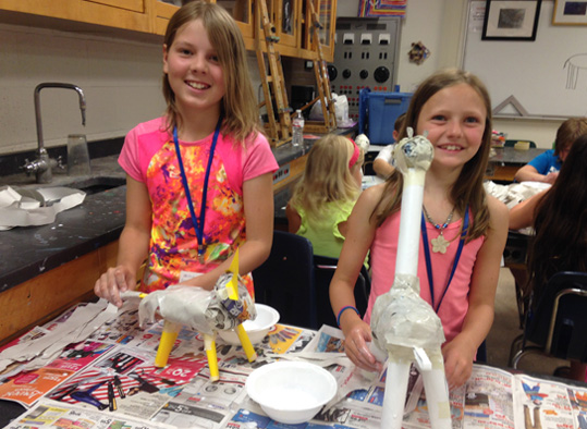 Students showing off their paper mache projects.