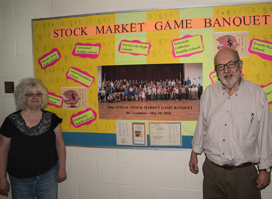 BC3 Center for Economic Education directors stand in front of the Stock Market Game Banquet bulletin board.