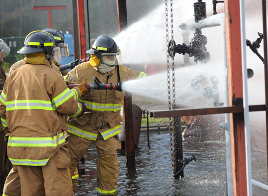 Student firefighters use a hose to put out a fire