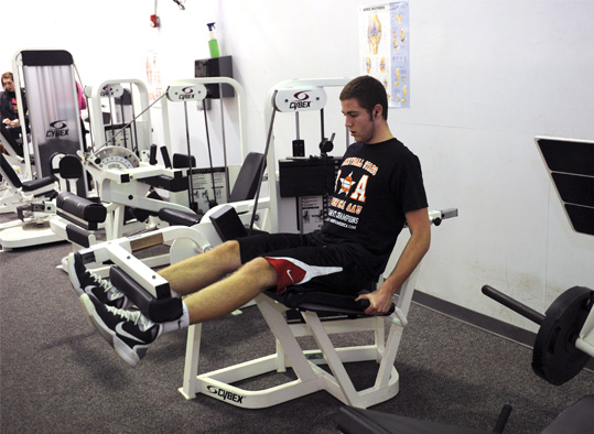 Student lifting leg weights on a machine