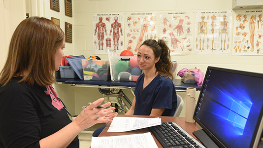 a student and advisor meet in healthcare classroom