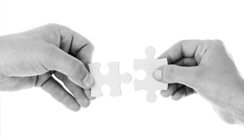 Two hands working together to put two puzzle pieces together.