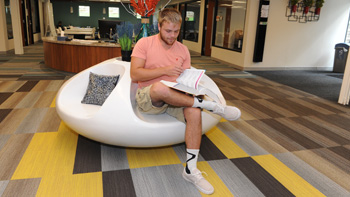 A student sitting on a circular seat on the bottom floor of the Heaton Family Learning Commons.