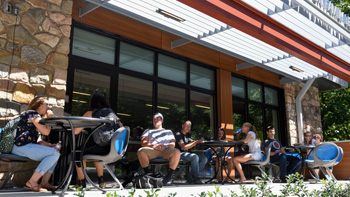 Students sitting on the patio of the Heaton Family Learning Commons.